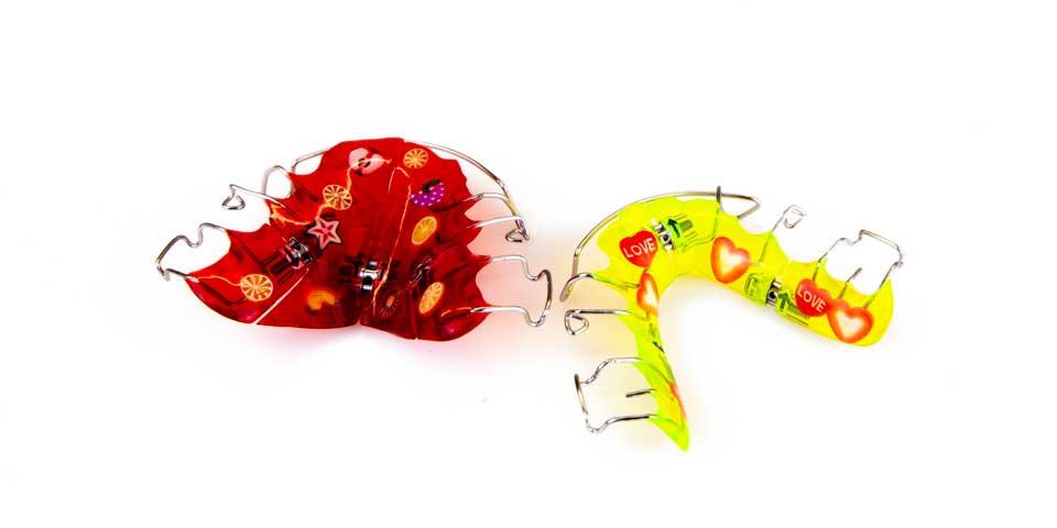 Zwei kieferothopädische heruasnehmbare Zahnspangen in rot und gelb